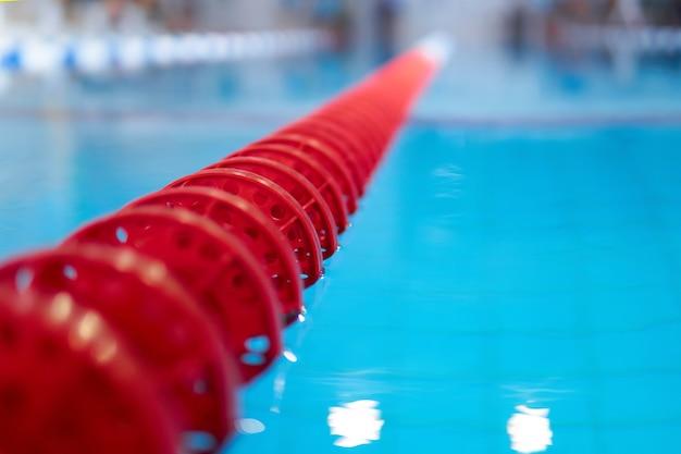 Hintergrund - fragment des wettkampfbeckens mit blauem wasser und markierten schwimmbahnen