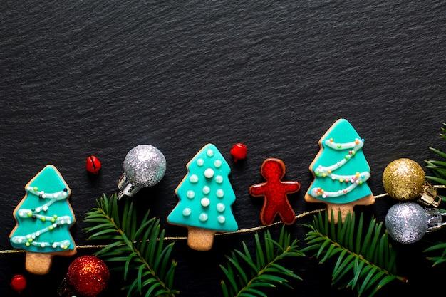 Hintergrund für pastellweihnachtsplätzchenbaum des feiertagslebensmittels diy auf schwarzem schieferbrett