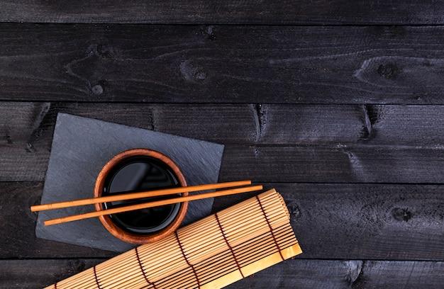 Hintergrund für sushi. bambusmatte und sojasauce auf schwarzem holztisch. draufsicht mit kopierraum