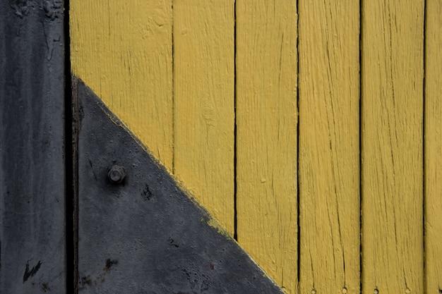 Hintergrund holz textur mit schwarzem türscharnier. alte gelb gestrichene bretter. detail des scharniers an der alten holztür