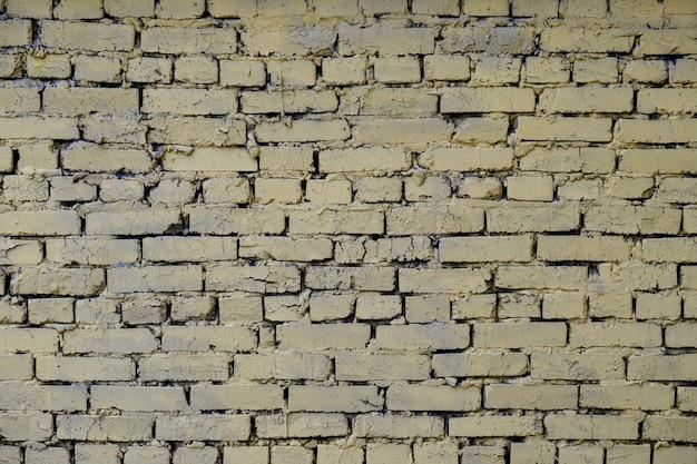 Hintergrund in der industriellen art des gemalten gelben gebrochenen ziegelsteines.