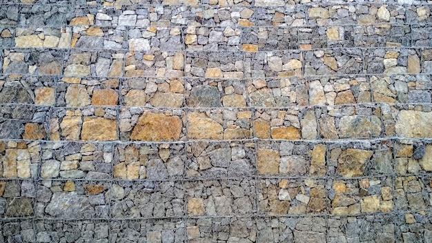Hintergrund in form von gestapelten steinen und mit gewebtem metallgitter befestigt