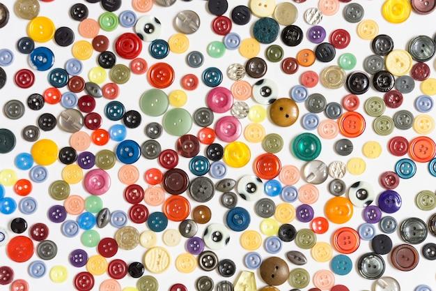 Hintergrund - mehrfarbige einfarbige knöpfe chaotisch angeordnet auf einer weißen fläche