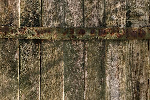 Hintergrund mit altem holzzaun mit metallvorhang. textur der alten bretter.
