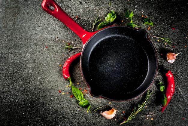 Hintergrund mit bratpfanne und gewürzen kochen - pfefferknoblauchbasilikum-rosmarinsalzschwarz-steintabelle