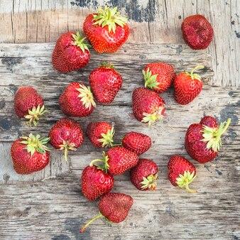 Hintergrund mit einer roten reifen erdbeere auf einem hölzernen brett