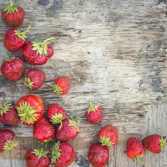 Hintergrund mit erdbeere auf einer strukturierten holzoberfläche mit spindel
