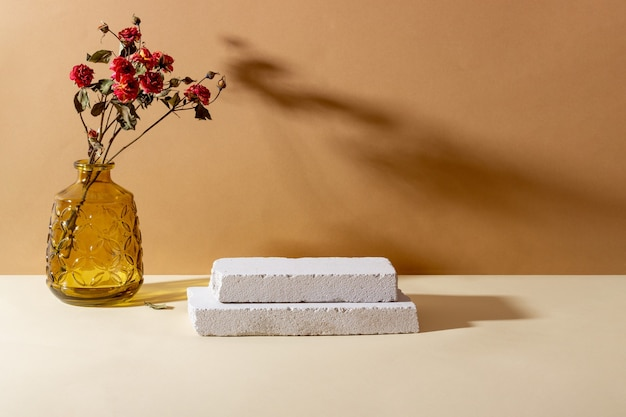 Hintergrund mit geometrischen formen aus beton für kosmetische produkte. rechteckige podeste, glasvase mit getrockneten blumen und schatten auf beigem hintergrund. leeres modell für produkt
