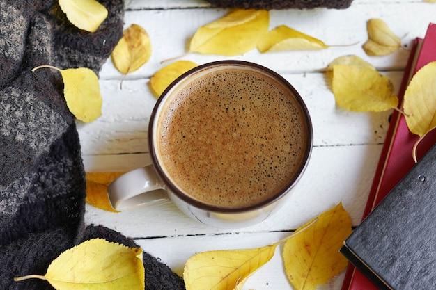 Hintergrund mit herbstlaub und heißer kaffeetasse. gelbe gefallene herbstblätter