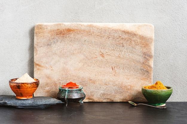 Hintergrund mit leerem schneidebrett und verschiedenen orientalischen gewürzen