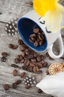 Hintergrund mit leerer blauer kaffeetasse und bohnen