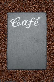 Hintergrund mit rahmen aus gerösteten braunen kaffeebohnen und stein-servierbrett mit handgeschriebenem kreidezeichen