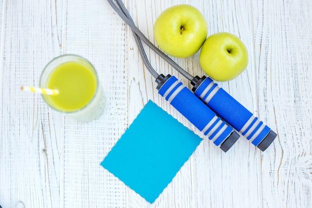Hintergrund mit saft, äpfeln und einem springseil