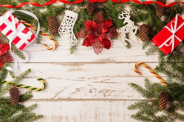 Hintergrund mit traditionellen geschenken in festlicher verpackung, karamellrohr, rote blume. weißer hölzerner hintergrund mit zweigen und zapfen der fichte.