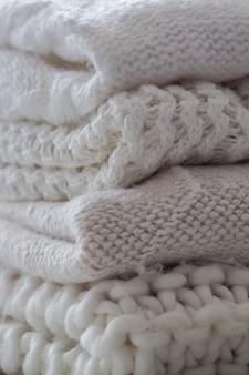 Hintergrund mit warmen pullovern. stapel gestrickter kleidung in warmen farbtönen
