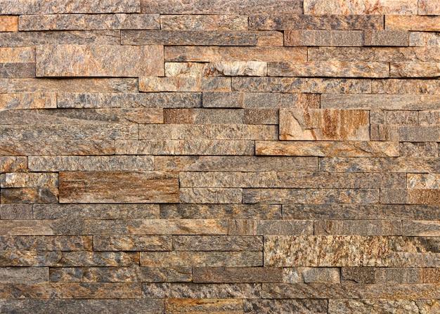 Hintergrund oder textur einer steinmauer aus gelbem schiefer aus naturstein.
