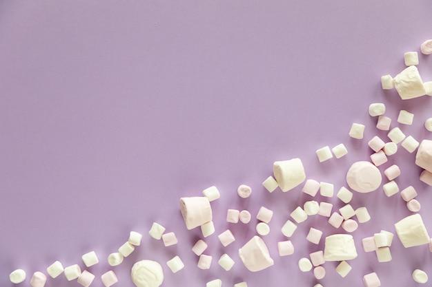 Hintergrund oder textur von rosa und weißen mini-marshmallows auf lila hintergrund mit freiem platz für text