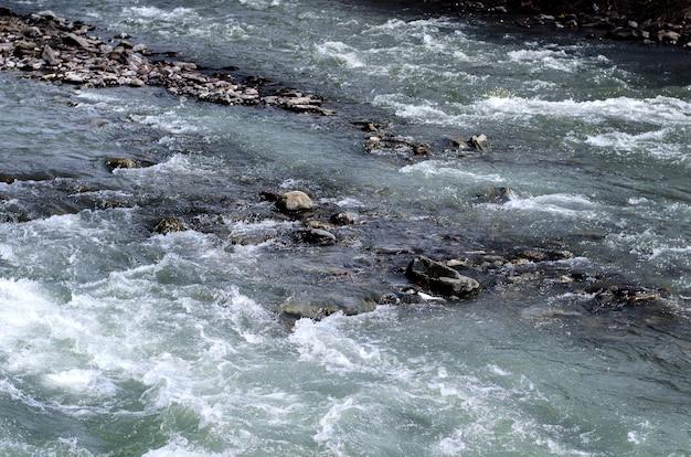 Hintergrund. schneller gebirgsfluss. unter steinen.