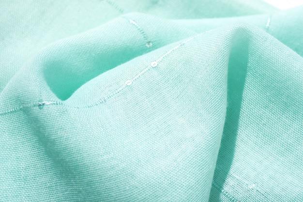 Hintergrund und textur baumwollgewebe von minze farbe mit kleinen pailletten liegt mit falten.