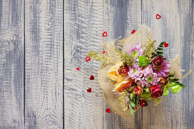 Hintergrund valentinstag oder hochzeit. korbstrauß von rosen und chrysanthemen auf einem weinlesehölzernhintergrund.