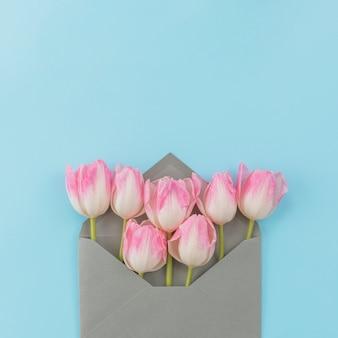 Hintergrund verziert durch tulpen im umschlag