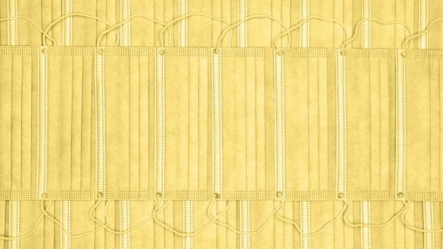 Hintergrund vieler chirurgischer gesichtsmasken. nahaufnahme der medizinischen atembandage für das menschliche gesicht mit gummi-ohrbändern. abstrakte medizin hintergrundfärbung im trend mellow yellow farbe des jahres 2021