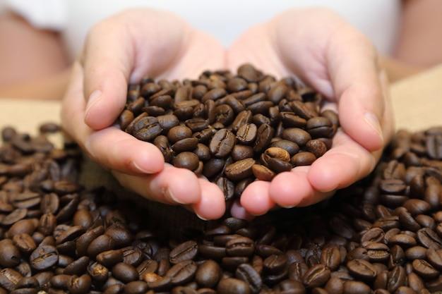 Hintergrund von den röstkaffeebohnen, die aus schalenförmigen händen in einen leinwandsack heraus gießen