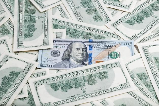 Hintergrund von dollar. noten von einhundert us-dollar sind im hintergrund verstreut.