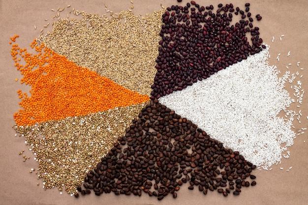 Hintergrund von dreiecken, die mit verschiedenen getreidesorten und nüssen auf einem kraftpapier ausgekleidet sind.
