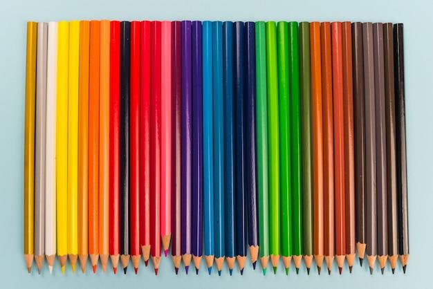 Hintergrund von farbstiften auf blauem papier. bunte linie von buntstiften.