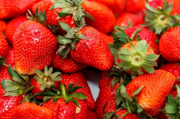 Hintergrund von frischen erdbeeren, gerade im garten gepflückt. frische saftige erdbeere - gefüllter rahmen