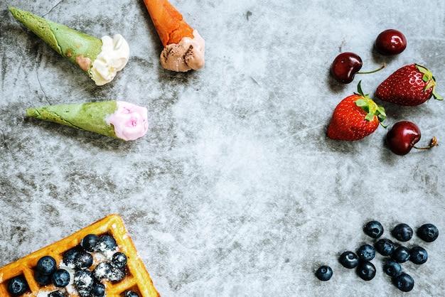 Hintergrund von geschmackvollen und süßen nahrungsmitteln mit roten früchten und waffeln