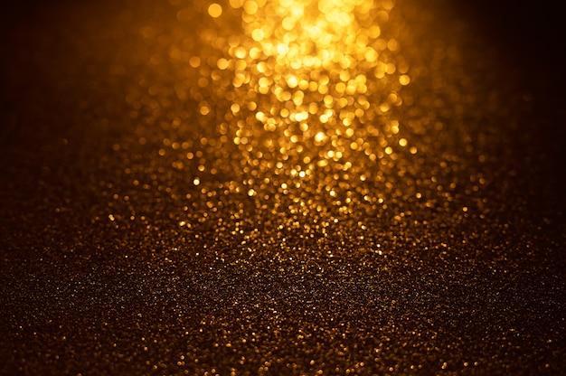 Hintergrund von goldenen und schwarzen glitzerlichtern defokussierter abstrakter hintergrund
