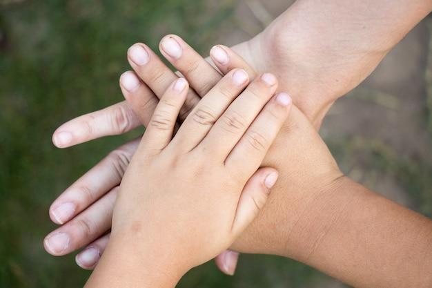 Hintergrund von händen des asiatischen weiblichen erwachsenen und zwei kinder gruppieren zusammen für unterstützung