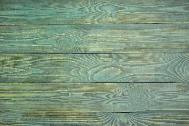 Hintergrund von hölzernen beschaffenheitsbrettern mit den resten der hellgrünen farbe. horizontal.