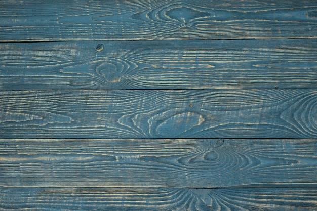 Hintergrund von hölzernen beschaffenheitsbrettern mit resten der blauen farbe. horizontal.