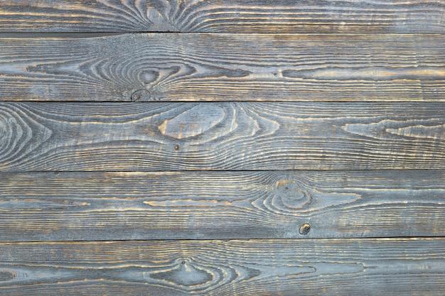 Hintergrund von hölzernen beschaffenheitsbrettern mit resten der grauen farbe. horizontal.