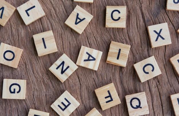 Hintergrund von holzdruckdruckblöcken des buchdrucks auf hölzernen, zufälligen buchstaben des alphabets und der durch schwarze tinten befleckten interpunktion