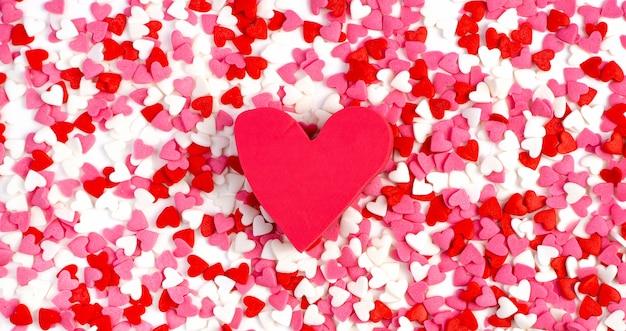 Hintergrund von kleinen farbigen herzen und einem großen rosa herzen. der blick von oben. valentinstag