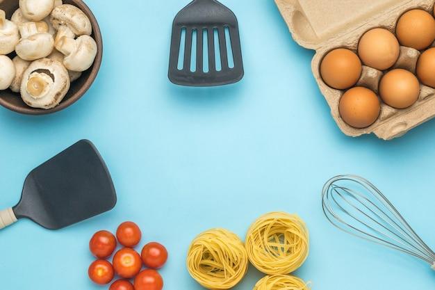 Hintergrund von küchenzubehör und pasta-zutaten auf blauem grund. zutaten für die herstellung von nudeln. platz für text.