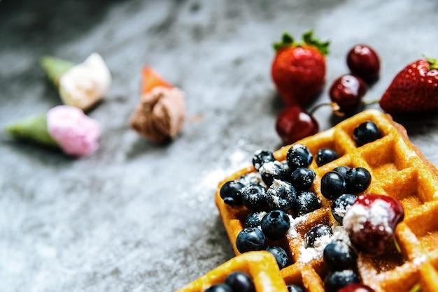 Hintergrund von lebensmitteln, die eiscreme in zapfen mit roten früchten und waffeln erfrischen