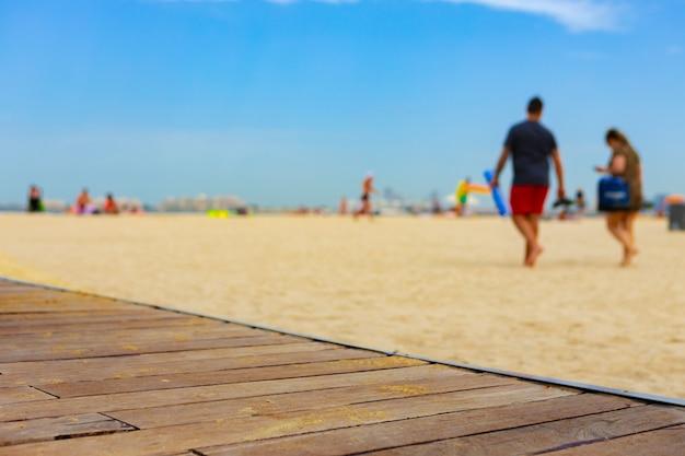 Hintergrund von leuten, die an einem sonnigen tag am strand spazieren gehen
