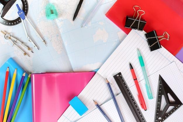 Hintergrund von notebooks, einer konturkarte der welt und bürobedarf