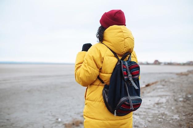 Hintergrundansicht einer jungen touristin mit einem rucksack, der auf der seitenstraße zwischen dem riesigen leeren wintertal-tiefland geht. weiblicher reisender, der gelbe jacke und roten hut trägt. trampen, reisekonzept.