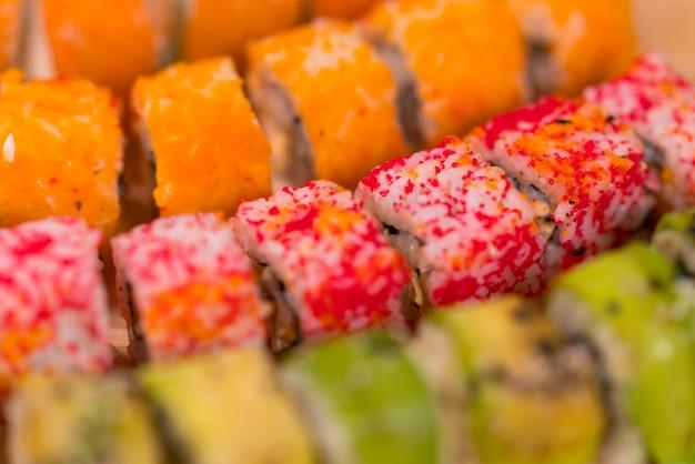 Hintergrundbeschaffenheit der bunten sushi-rollen mit frischem rohem fisch, reis und seetang in einer vollbildansicht