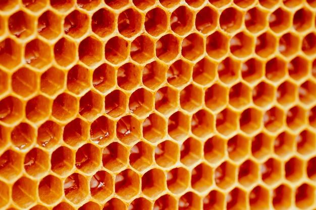 Hintergrundbeschaffenheit und muster eines abschnitts der wachswabe von einem bienenstock, der mit gold gefüllt wird