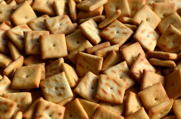 Hintergrundbeschaffenheit von den kleinen essbaren quadraten gebacken vom teig und mit salz besprüht. viel salzknacker