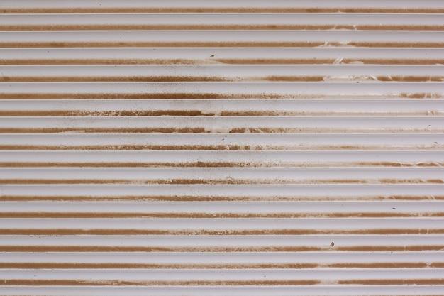 Hintergrundbeschaffenheit von plastikjalousien, die mit staub und schmutz bedeckt sind