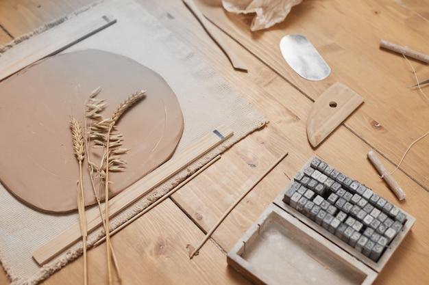 Hintergrundbild der rohen pflanzenabdruckkeramik auf holztisch in der töpferwerkstatt, kopierraum