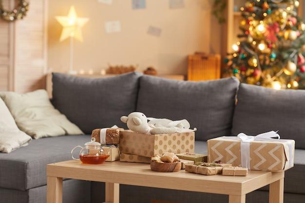 Hintergrundbild des gemütlichen hauptinnenraums mit weihnachtsgeschenken auf tisch im vordergrund, kopienraum